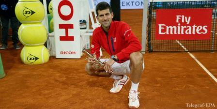 epa05295374 Serbian tennis player Novak Djokovic celebrates with the winner's trophy his victory 6-2, 3-6 and 6-3 against Scottish Andy Murray during their Mutua Madrid Open male final match played at the Caja Magica tennis complex in Madrid, Spain, on 08 May 2016.  EPA/JUANJO MARTIN